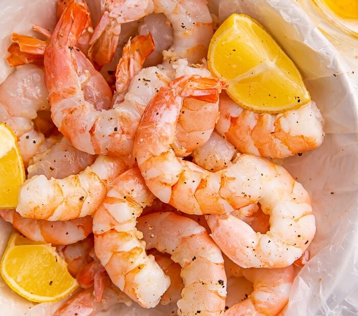 Instant Pot shrimp and lemon wedges inside a bowl lined with parchment paper