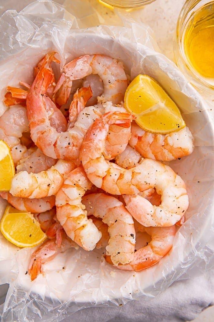 Instant Pot shrimp and lemon wedges inside a bowl lined with parchment paper
