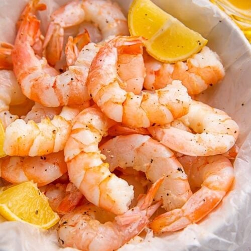 Instant Pot shrimp in a white bowl with lemon wedges