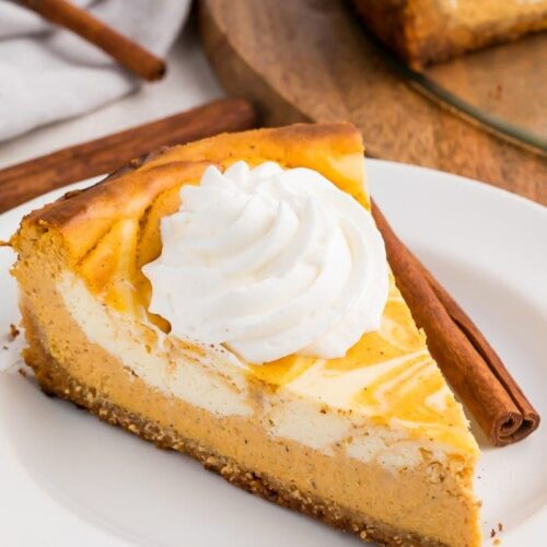 A slice of keto pumpkin cheesecake with a dollop of whipped cream on a white plate with a cinnamon stick