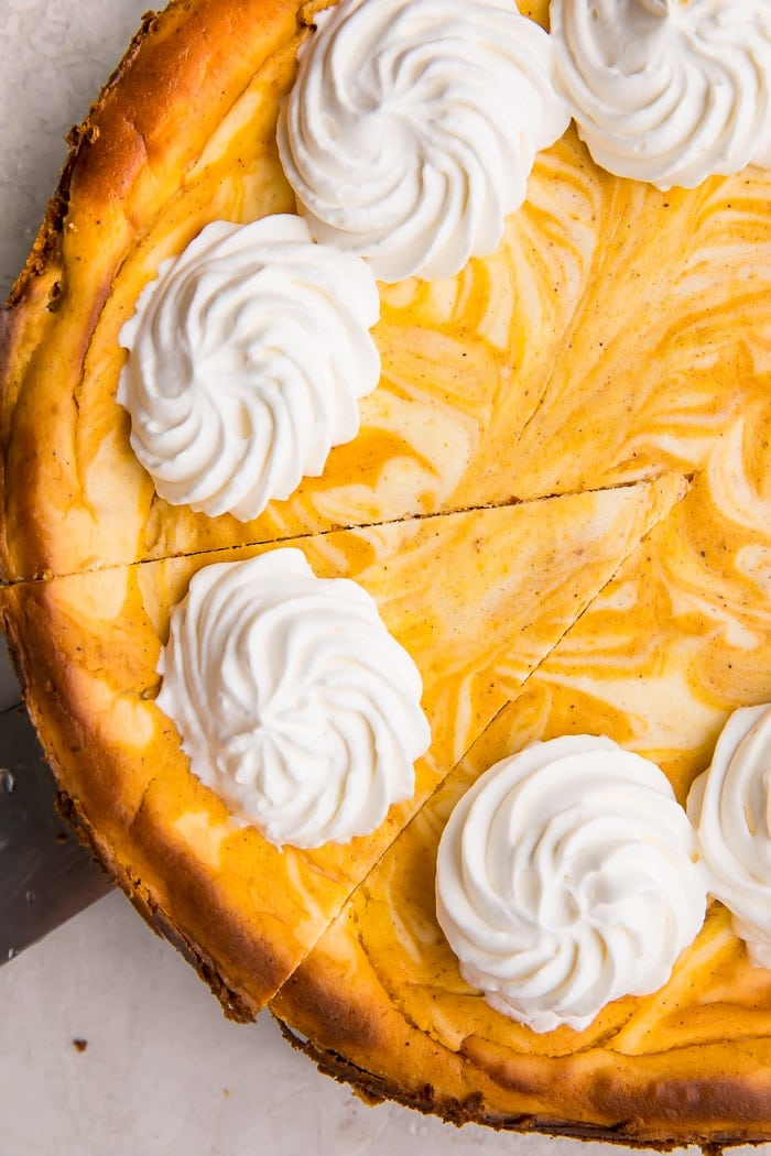 Keto pumpkin cheesecake with a swirled top and dollops of whip cream on top