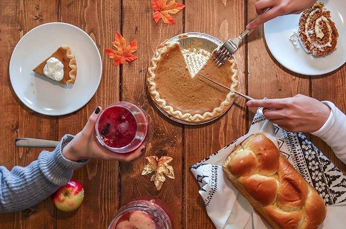 A Thanksgiving table with one hand holding a drink and another cutting a pie