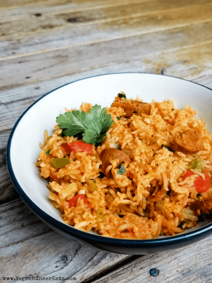 Vegetarian jambalaya in a dark bowl with white interior on a wooden table