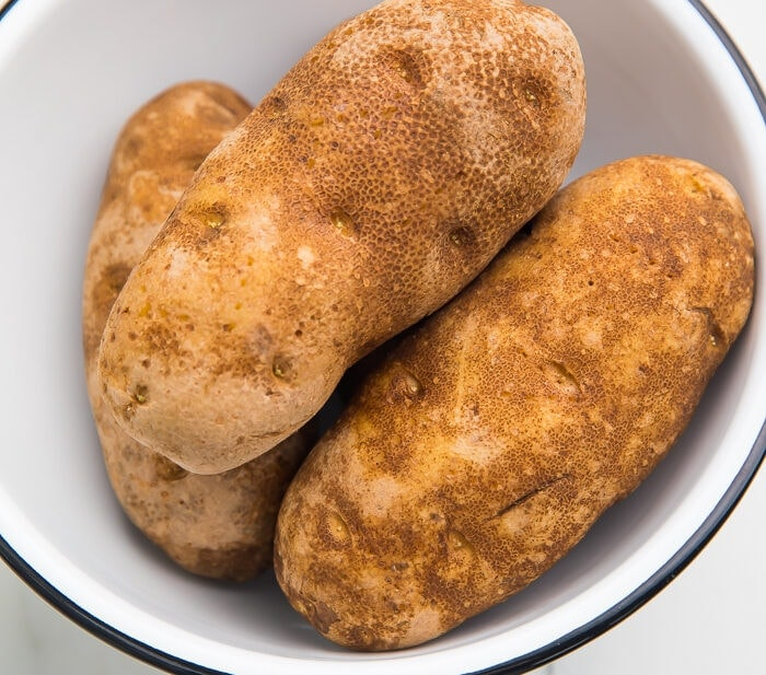 3 unpeeled russet potatoes in a black rimmed white bowl on a marble countertop