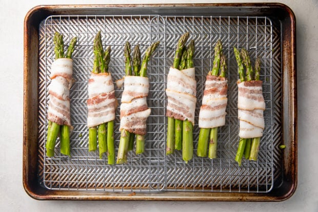 Uncooked asparagus spears wrapped in raw bacon laid perpendicularly on a wire rack over baking sheet