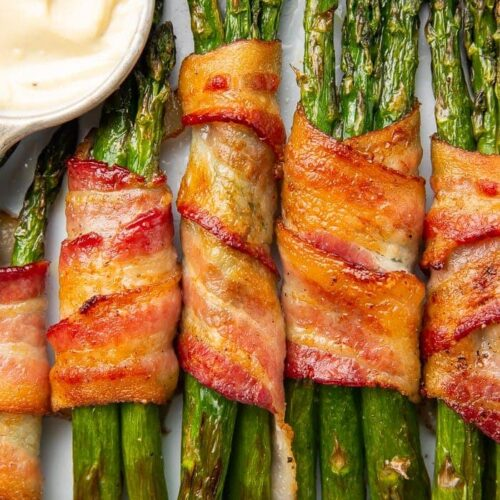 Bacon-wrapped asparagus stalks placed vertically in a row