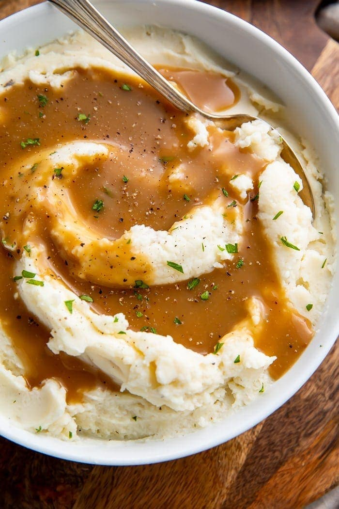 Mashed potatoes in a bowl with a spoon swirled with brown gravy