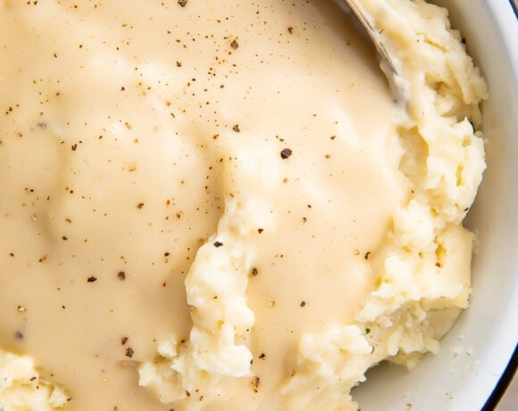 Overhead shot of chicken gravy over mashed potatoes in a white bowl with a spoon