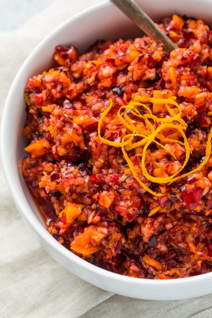 Cranberry orange relish in a white bowl with a silver spoon on a white napkin