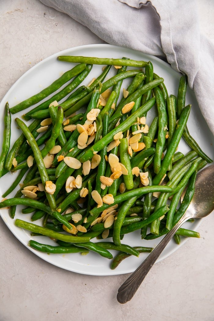 Green beans with almonds on a white platter with a silver fork and white napkin