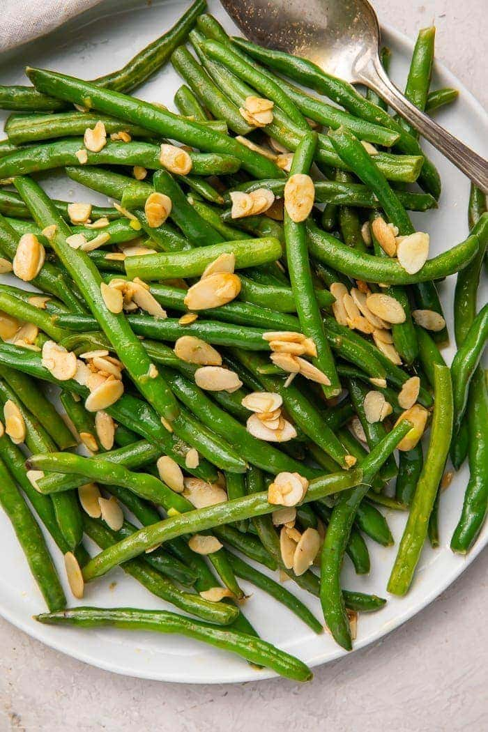 Green beans with almonds on a white platter