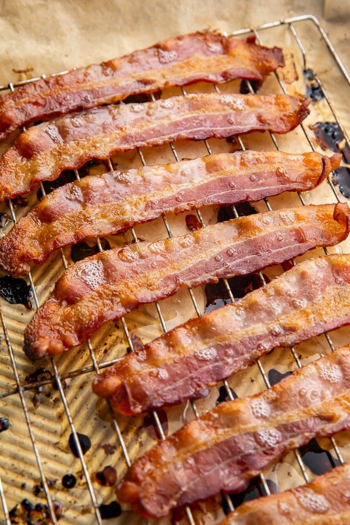 Crispy oven-cooked bacon on a silver cooling rack lined with parchment paper