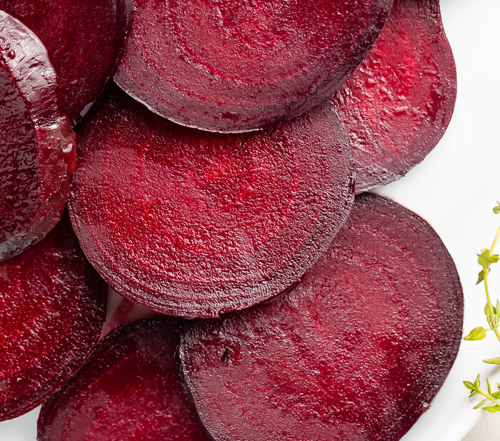 Dark red beets cut into medallions displayed on a white dish