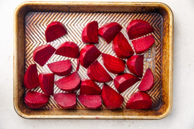 Dark reed beets cut into wedges and placed on silver sheet pan