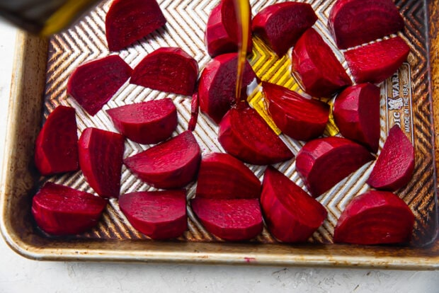 Dark red beet wedges covered with extra virgin olive oil on silver sheet pan