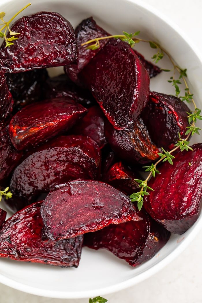 Deep red beets with green garnish in a white bowl
