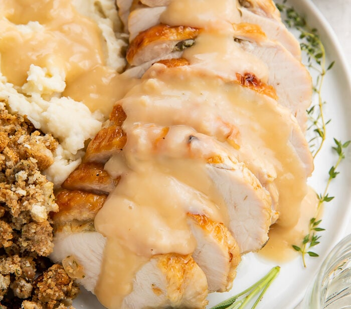 Instant Pot turkey breast slices covered with gravy on a plate