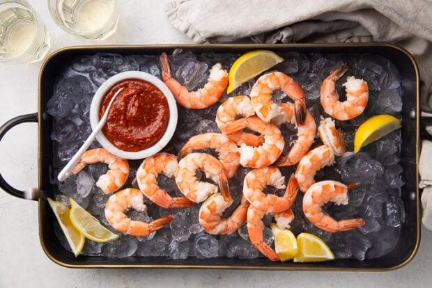 Black platter with boiled shrimp, shrimp cocktail sauce, ice, and lemon.
