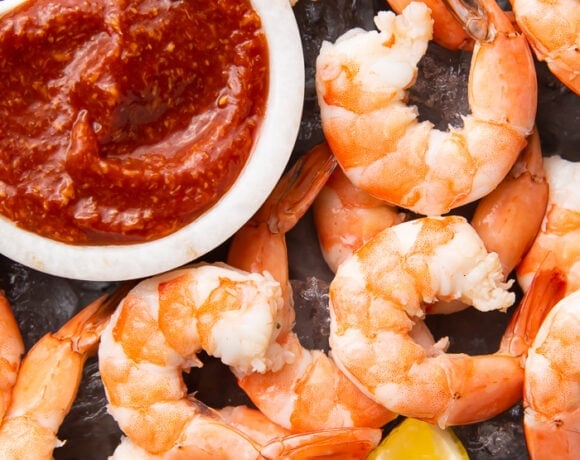 Shrimp cocktail sauce in a white ramekin on a black platter surrounded by peeled shrimp