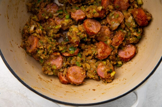 Chopped vegetables and andouille sausage mixed in a roux in a heavy pan