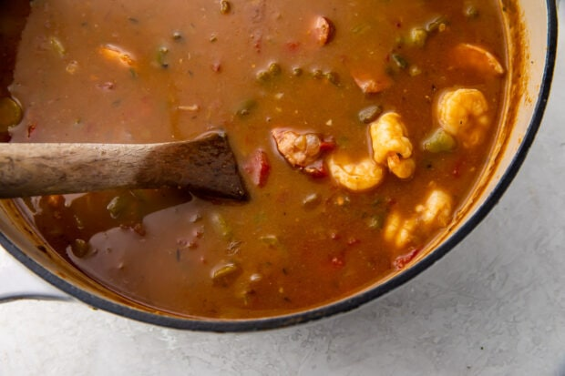 Broth, roux, vegetables, andouille sausage, and shrimp in large saucepan with wooden spoon on white countertop
