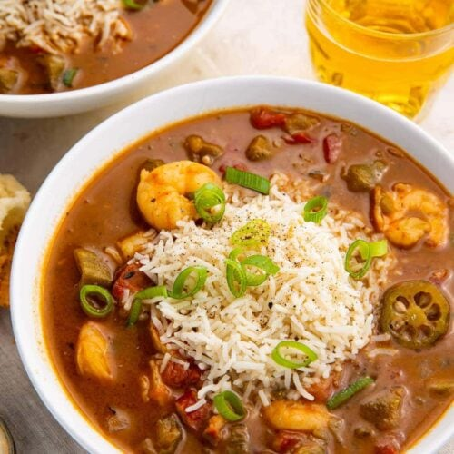Two bowls of shrimp and andouille gumbo on a white background