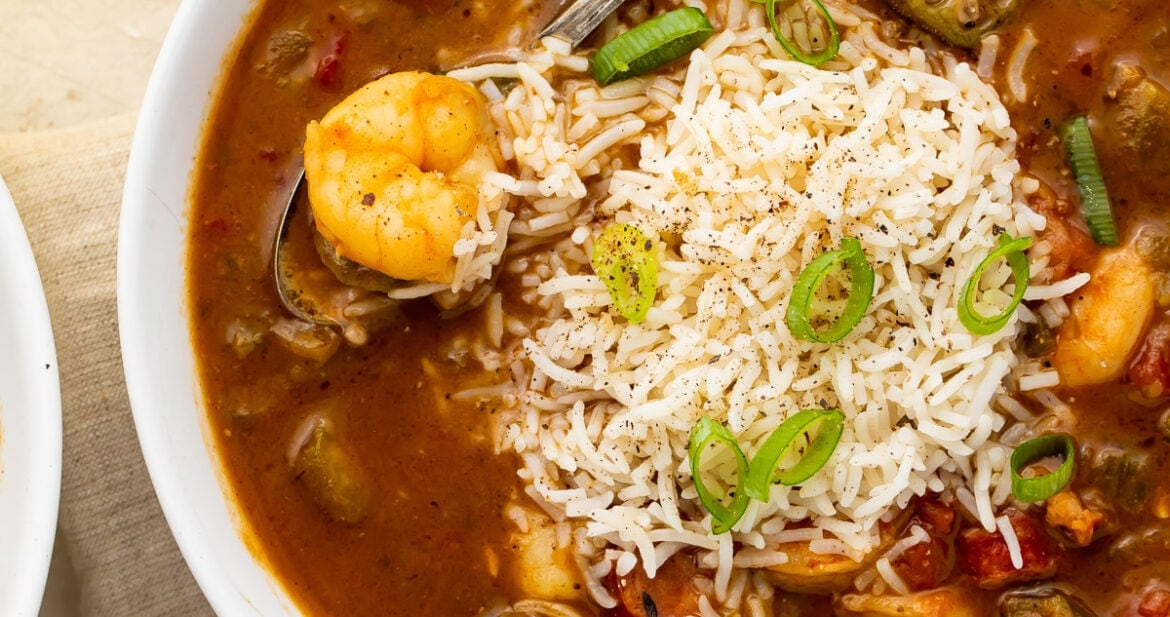 White bowl of shrimp and rice gumbo with a silver spoon surrounded by pieces of bread on a grey napkin with a glass of tea on a white countertop
