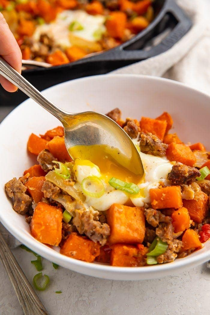 A spoon dipped into a white bowl of sweet potato hash