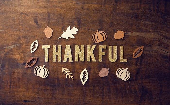 Thankful spelled on in cut-out letters on a wooden table