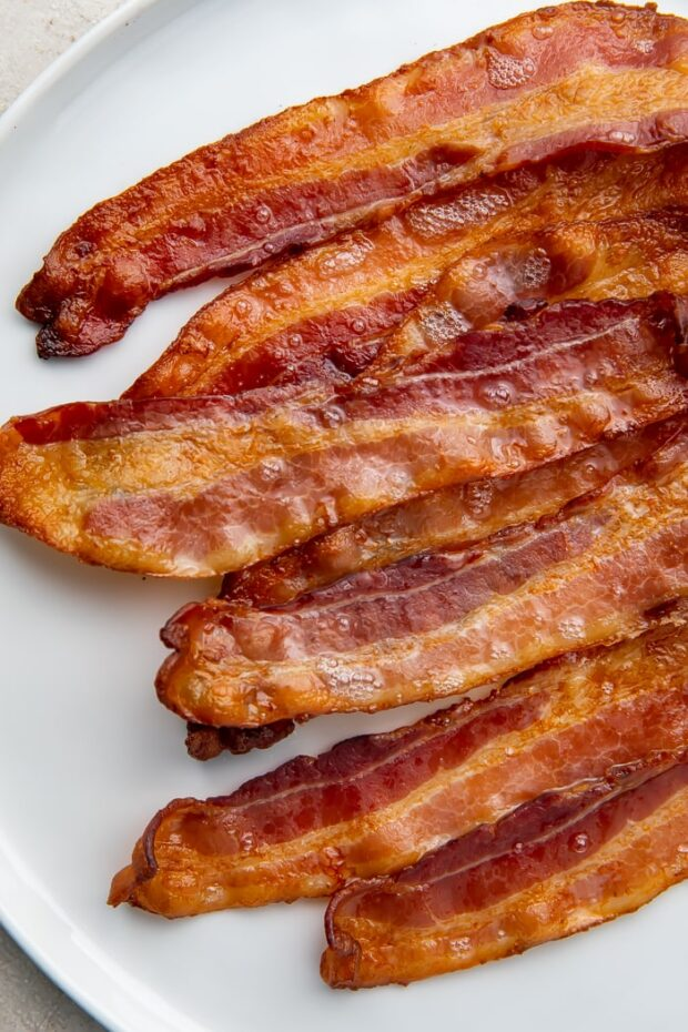 Strips of oven-cooked bacon on a white plate