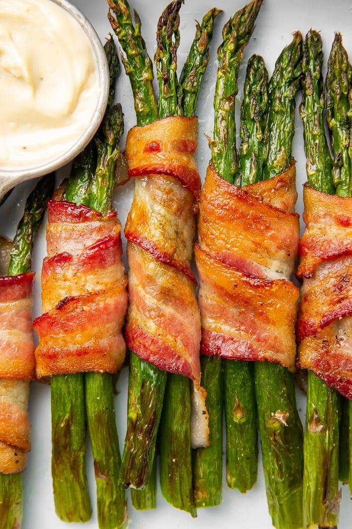 Whole30 asparagus wrapped in bacon served with garlic aioli