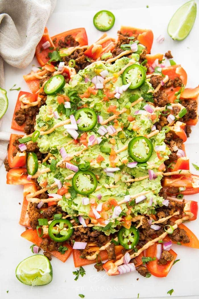 A giant platter of bell peppers, ground beef, guacamole, and other nacho toppings