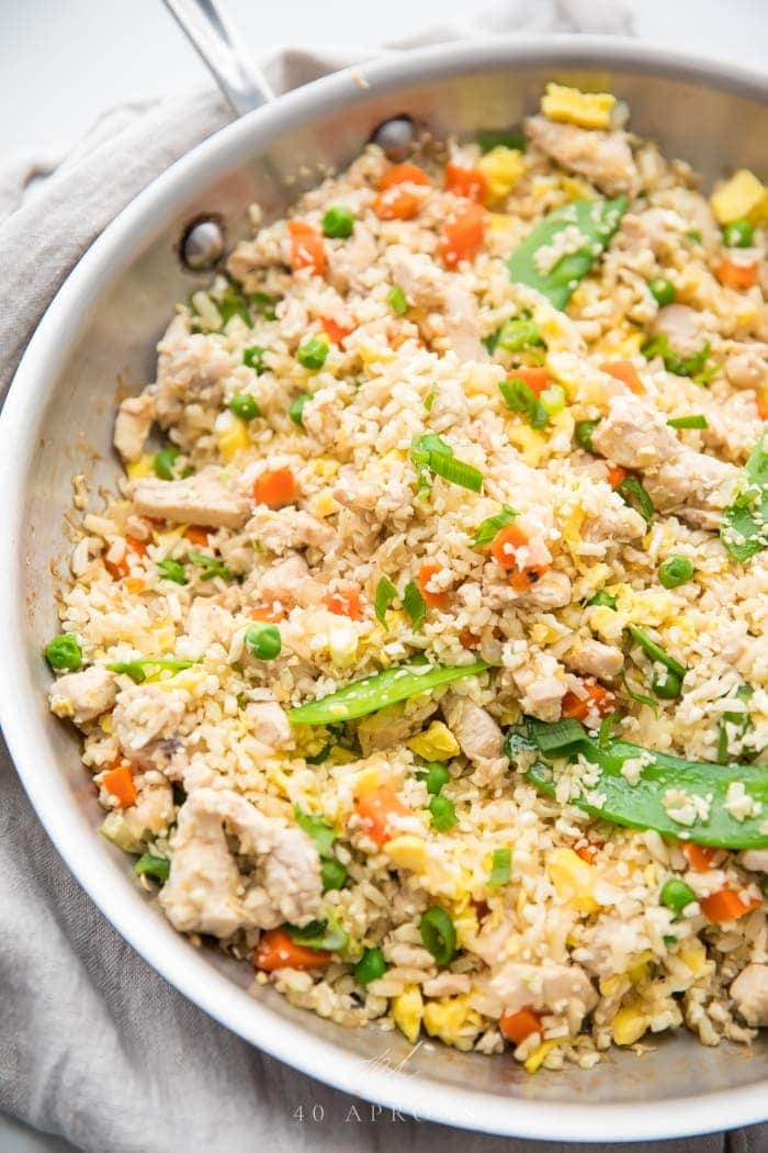 A large white bowl of cauliflower fried rice, veggies, and chicken
