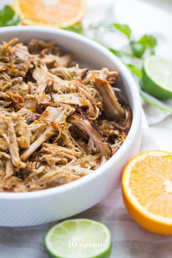 A white bowl with carnitas cooked in a Crockpot surrounded by cut citrus