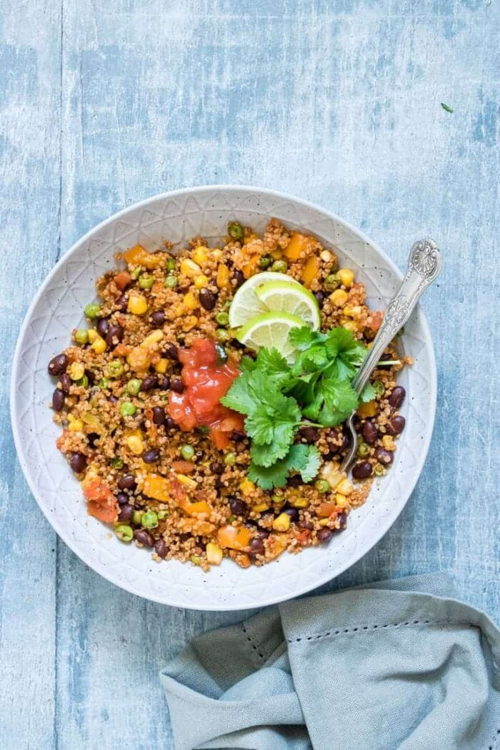 Instant Pot vegetarian Mexican quinoa in a white bowl against a blue background