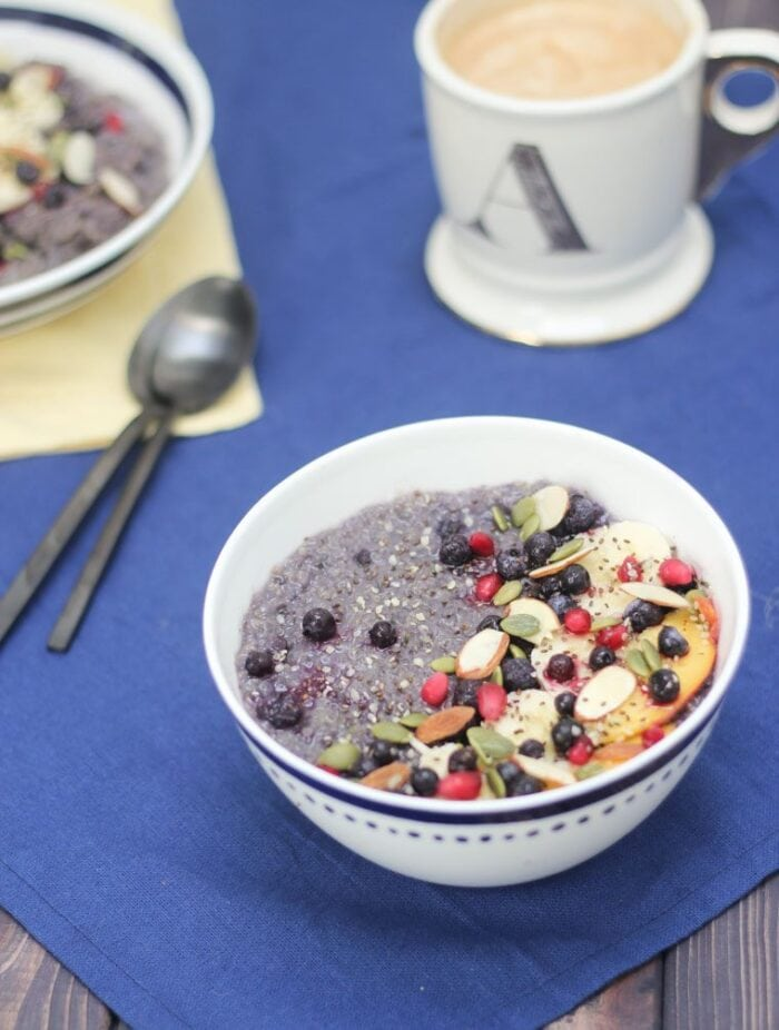 A white bowl of blueberry vegetarian slow cooker quinoa with fruits and slivers of almonds on a blue tablecloth