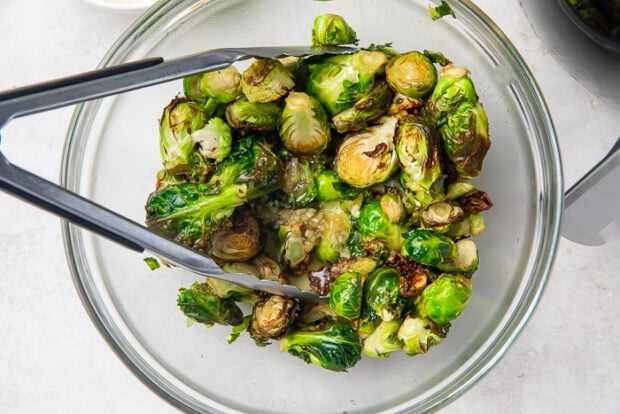 Brussels sprouts in a clear glass bowl with tongs