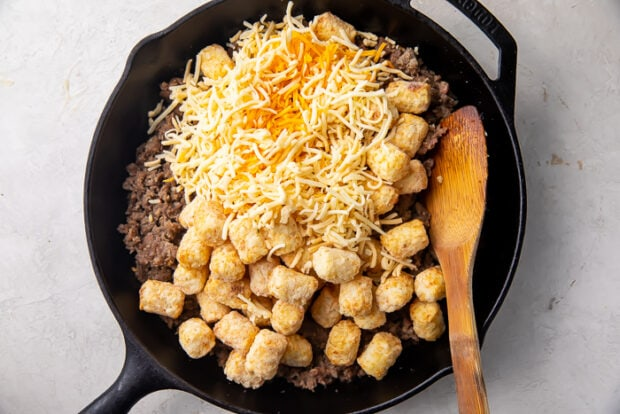Cast iron skillet with shredded cheese, sausage, and tater tots