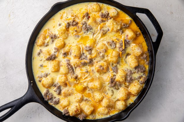 Uncooked tater tot breakfast casserole in a cast iron skillet