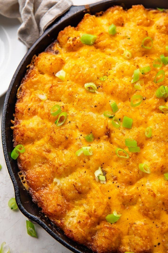 Cast iron skillet holding a tater tot breakfast casserole with cheese, sausage, and eggs, topped with chives