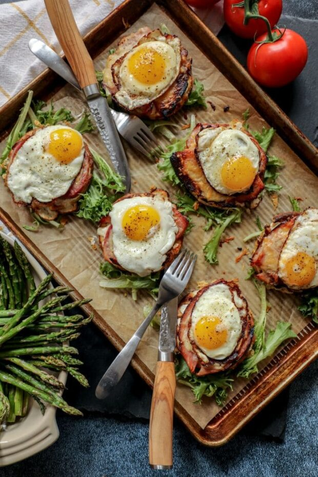 A sheet pan with croque madame, garnish, and silverware
