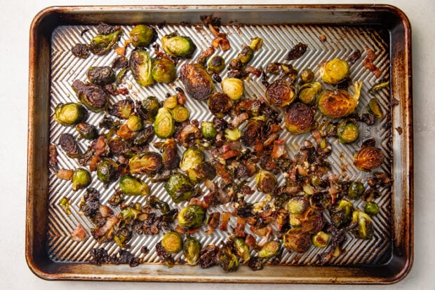 Oven roasted brussels sprouts with bacon on a silver sheet pan