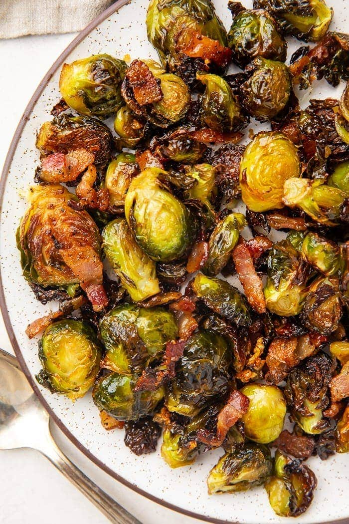 Dark trimmed white plate full of roasted brussels sprouts and bacon