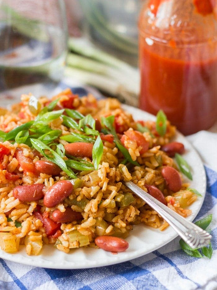 A plate of vegetarian slow cooker jambalaya with a fork on a blue and white tablecloth