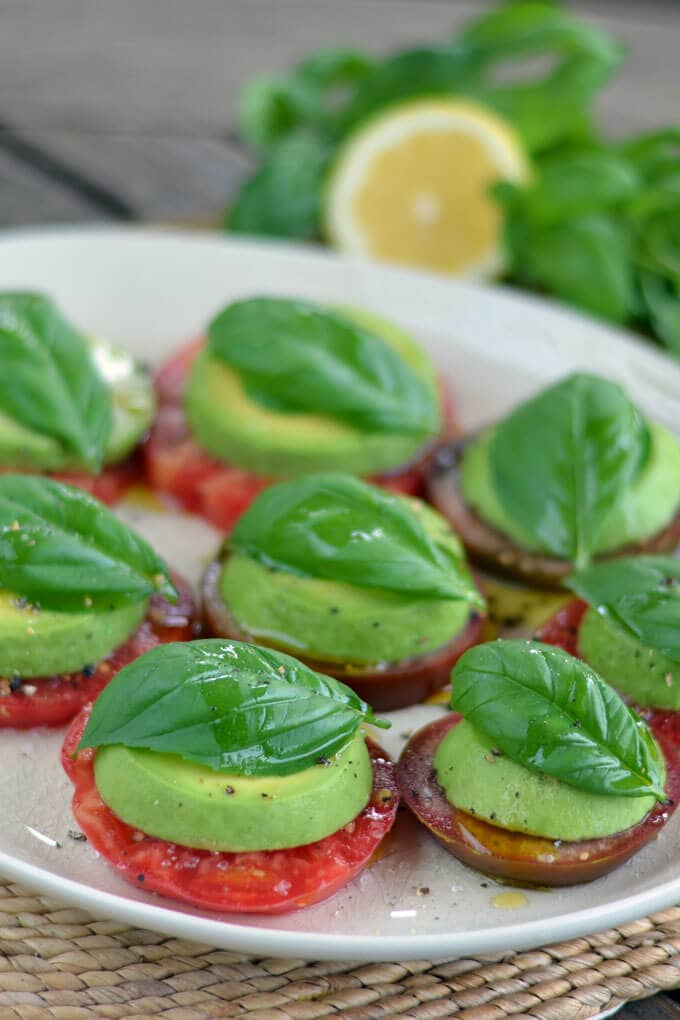 Tomato and avocado caprese on a white serving platter