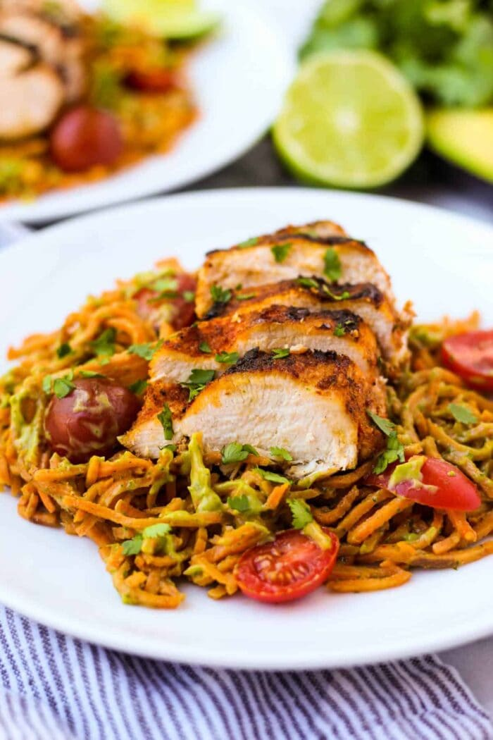 Whole30 chili dusted chicken with sweet potato noodles and avocado sauce on a white plate