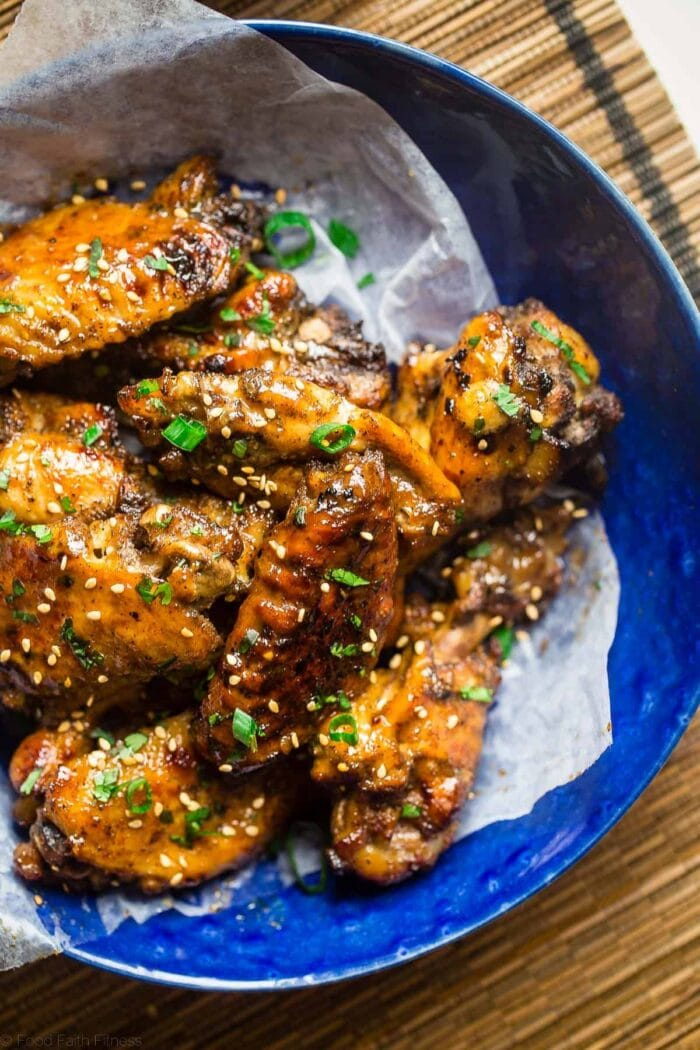 A blue ceramic bowl on a bamboo placemat holds glazed chicken wings with green onions