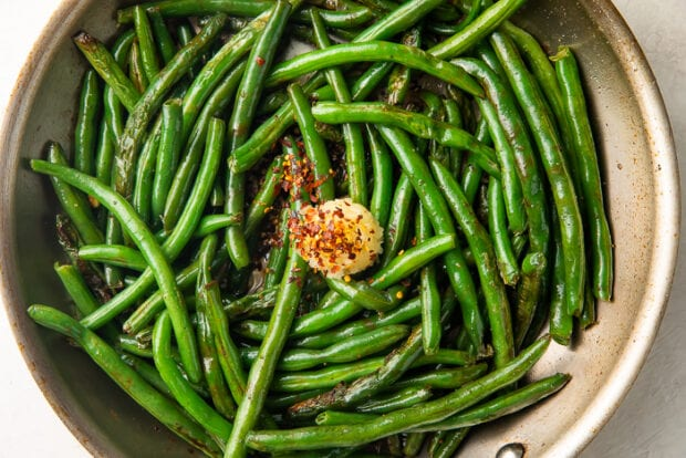 Green beans in skillet with garlic and red pepper flakes