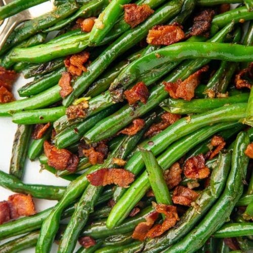 Close up of green beans with bacon on a white plate