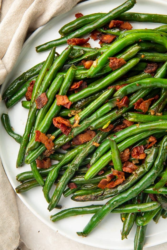 White plate holding sauteed green beans and bacon
